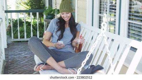 Mixed race woman texting and drinking tea on porch