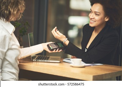 Mixed race woman using smartpay on her smart watch
