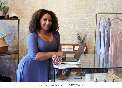 Mixed race woman working in clothes shop looking to camera