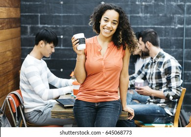 Mixed race worker looking at camera while her colleagues work