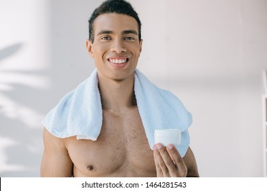 mixed race young man with blue towel on shoulders holding container with cosmetic cream while looking at camera