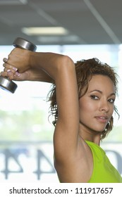 Mixed race young woman lifting weights at a gym