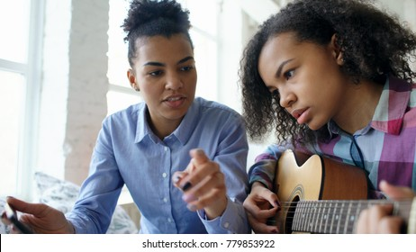 Mixed race young woman with tablet computer sitting on bed teaching her teenage sister to play acoustic guitar at home