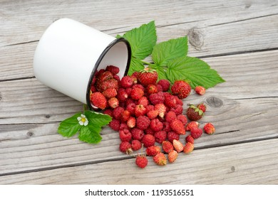 Mixed raspberries and strawberries scattered on a wooden table