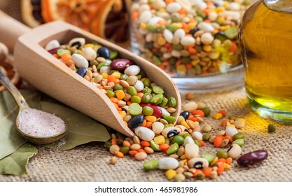 Mixed raw legumes, pulses in a wooden scoop, closeup view with details