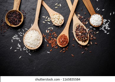 Mixed rice and Raw rice in wooden spoon over black desk background