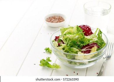 Mixed salad of iceberg, radicchio, endive, cabbage with flax seeds, oil and lemon on white wooden background for healthy diet.