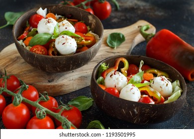 Mixed salad with mozzarella in coconut bowls close up