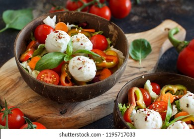 Mixed salad with mozzarella in coconut bowls close up