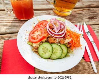 Mixed salad with red onion rings and beer, top view