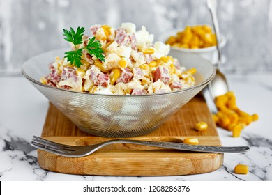 Mixed salad from salami sausage, cheese, boiled egg and canned corn with mayonnaise dressing