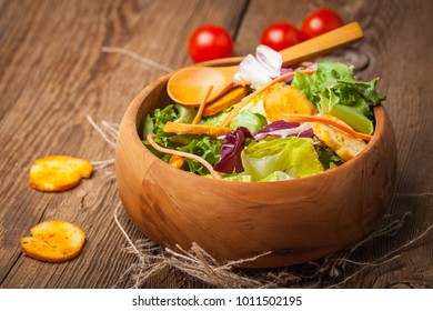 Mixed salad in a wooden bowl. Selective focus.