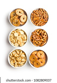 Mixed salty snack crackers and pretzels in bowls isolated on white background.