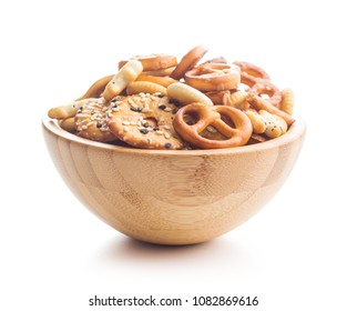 Mixed salty snack crackers and pretzels in bowl isolated on white background.