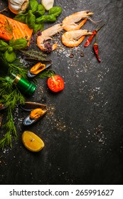 Mixed seafood being prepared in a kitchen with salmon steaks, pink prawns and mussels with fresh herbs and spices on a slate counter, view from above with copyspace