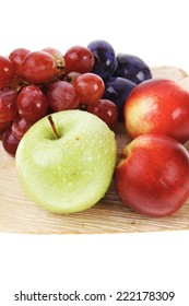 mixed set of fresh raw ripe fruits apple peach grape and plum on light wooden plate isolated over white background