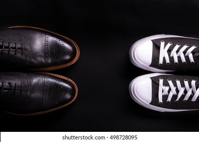 Mixed shoes. Oxford and sneakers shoe on black background.  Different style of men fashion. Compare of formal and casual. Top view. Copy space.