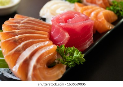 Mixed slices of fresh raw salmon sashimi served with wasabi for dinner. Fresh raw salmon fish sashimi is sliced / cut into pieces in Japanese cuisine. Assorted fresh sashimi & Japanses food concept.