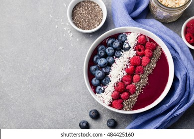 Mixed smoothie bowl with fresh raspberry, blueberry, coconut flakes and chia seeds. Grey stone background. Top view. Copy space