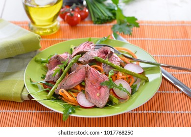 Mixed spring salad with roasted asparagus and medium fried beef steak cut into strips