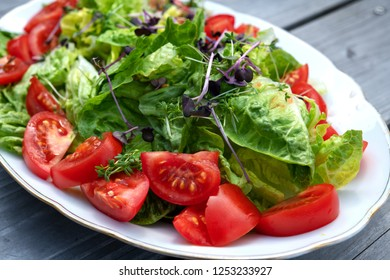 mixed summer salad on plate and wooden ground