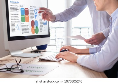 Mixed team of consultants working on a Business Plan report on computer screen with executive summary, strategy information data, SWOT, market analysis, and financial statement, consulting office