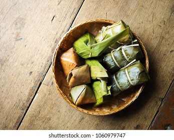 Mixed Traditional Thai Dessert wrapped with banana leaves in basket on wood table: Khanom Sai Sai(Sweentened Coconut Stuffed), Khanom Tian(Pyramid Stuffed Dough) and Kao Tom Mud(Banana in Sticky Rice.