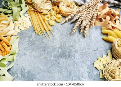 Mixed types and shapes of italian pasta on grey stone, background. Copy space.