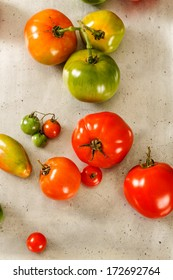 Mixed varieties of homegrown tomatoes rest on an old, worn vintage metal baking sheet.