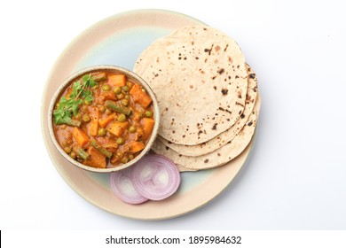 mixed veg curry made from beans, carrot, potato with roti or chappati on a plate, Indian food