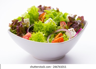 mixed vegetable salad with tomatoes, onions and feta cheese in a white bowl on white background