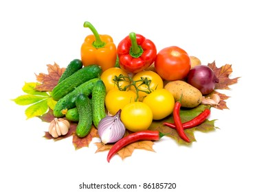 mixed vegetables and autumn leaves on a white background