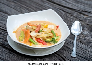 Mixed vegetables in creamy red curry coconut sauce with tofu in a white plate on a wooden table. Thai cuisine, traditional Thai food.
