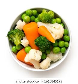 Gemisches Gemüse in weißer Keramikschüssel einzeln auf Weiß. Draufsicht.
