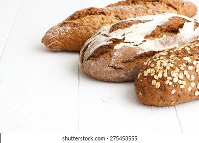 Mixed whole grain health breads on rustic white painted wood.