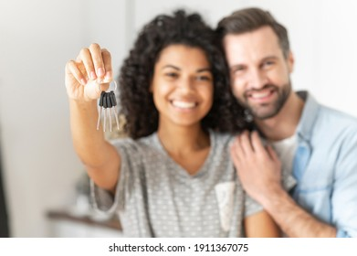 Mixed-race couple in love hugs in a new home holding the keys in a hands. Young multiracial family bought a new house, rent an apartment, got a mortgage. Focus on the keys