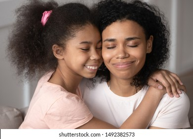 Mixed-race daughter embraces mother people closed eyes enjoy moment of tenderness and caress, adopted child express gratitude to new mom blessed to have family, children the greatest treasure concept