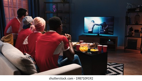 Mixed-race differente happy friends males and females sitting on couch in living room at home in evening watching sport program on TV, box fans cheering for favorite boxer. Entertainment concept