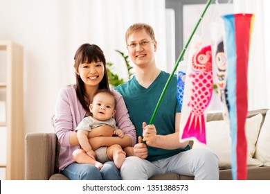 mixed-race family, children's day and asian holidays concept - happy mother, father and baby son with koinobori carp streamer celebrating tango no sekku at home