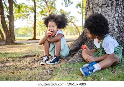 Mixed-race girl and boy eating red apple and have big smile face under the big tree. She relax and playing in the public. Learning ideas outside the classroom. Soft focus