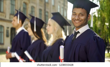 Mixed-race graduate student with diploma smiling into camera, exchange program