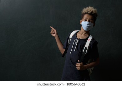 Mixed-race pretty school age boy wear facemask and backpack looking at camera standing indoors pose against black wall  point finger on dark grey background. Commercial advertisement concept