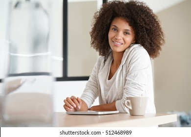 Mixed-race woman at home using tablet and drinking tea