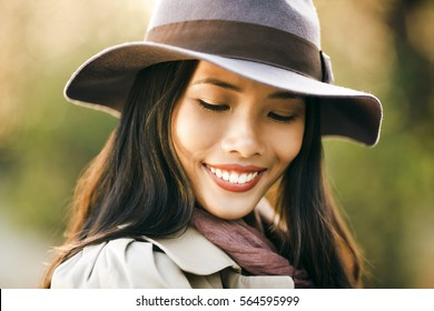 Mixed-race woman wearing a hat smiling outdoors.
