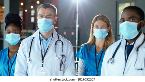Mixed-races specialists, males and females doctors in hospital. International medics in medical masks. Protected workers. Multi ethnic physicians and nurses. Clinic team. Protection. Camera moving. - Shutterstock ID 1819052207