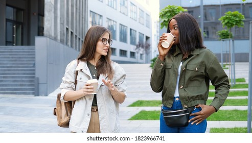 Mixed-races young pretty females, best friends talking cheerfully and walking with cups of coffee to-go and at city street. Multi ethnic beautiful happy women students strolling outside with drinks.