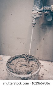 Mixer in a bucket with finished plaster, construction tools for finishing works