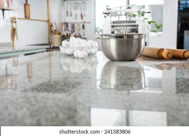 Mixing bowl with eggs and rolling pin on marble countertop in commercial kitchen