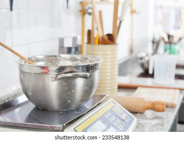 Mixing bowl on weight scale at counter in commercial kitchen