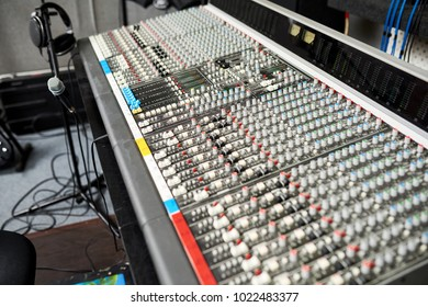 Mixing desk used for combining sounds of many different audio signals and microphone on stand with headphones in studio